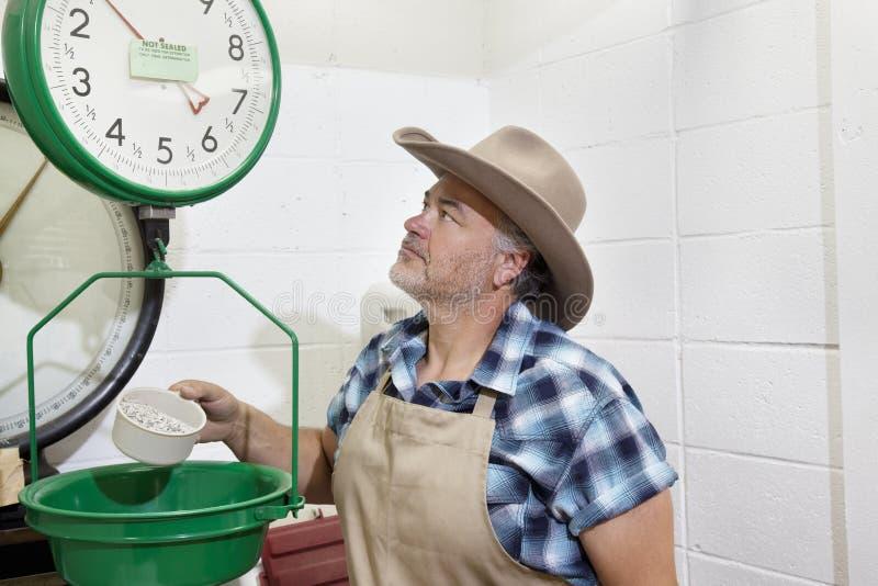 Rijpe cowboy die omhoog gewichtsschaal bekijkt royalty-vrije stock afbeeldingen
