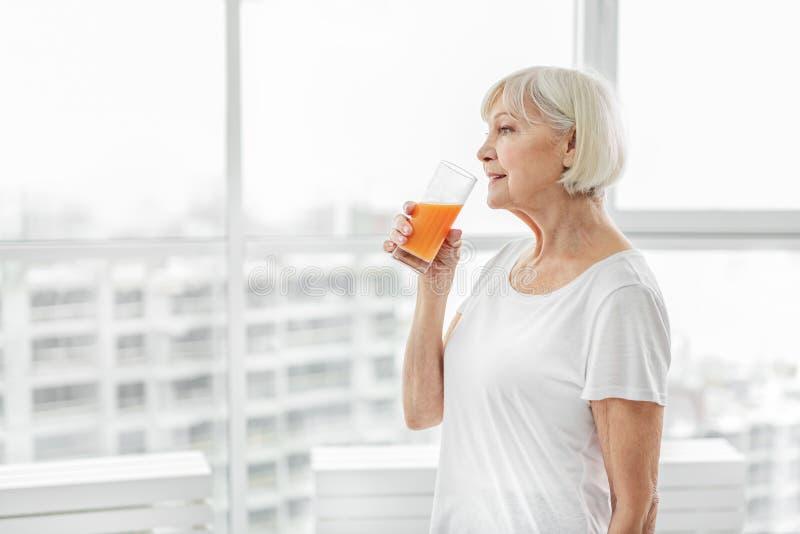 Rijpe dame die van gezonde drank genieten stock afbeelding