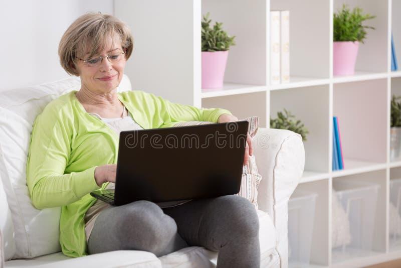 Rijpe dame met laptop stock fotografie