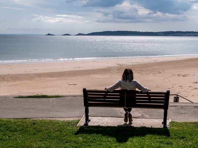 Rijpe damezitting die neer uit over de baai van Swansea kijken royalty-vrije stock foto's