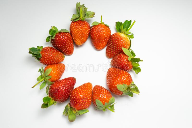 rijpe die aardbeien in een cirkel op een witte achtergrond worden gevouwen stock foto's