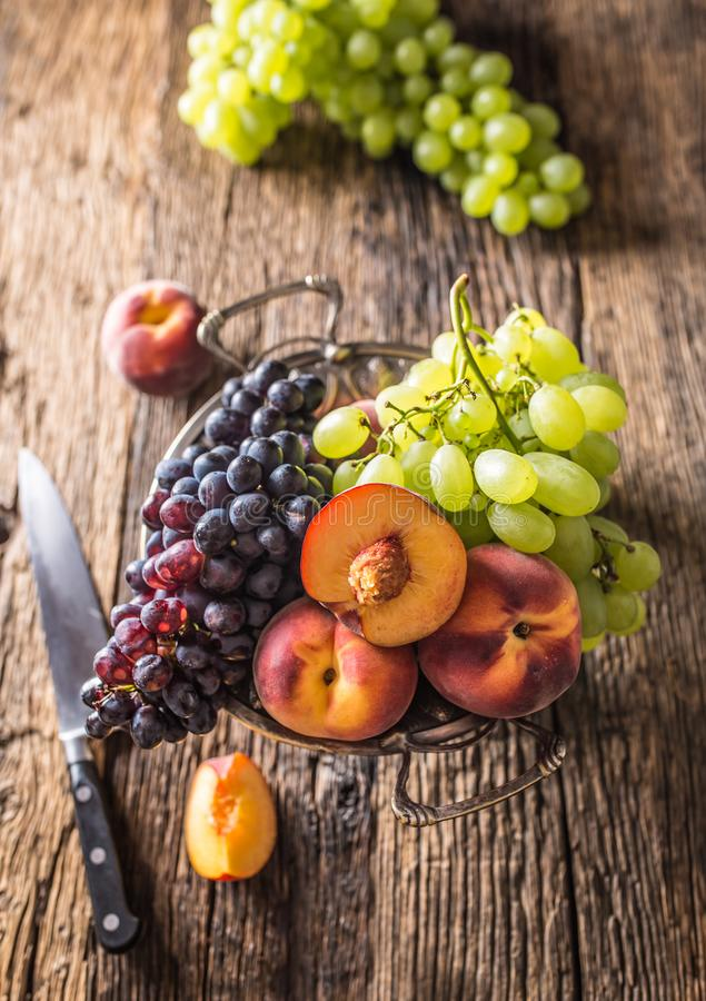 Rijpe druiven en perziken in rustieke kom en houten lijst royalty-vrije stock foto