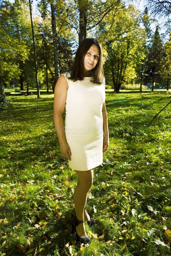 Rijpe echte donkerbruine vrouw in groen de lentepark, levensstijlconce royalty-vrije stock afbeelding