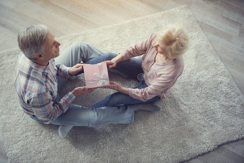 Rijpe echtgenoot die doos met gift overgaan tot vrouw stock afbeelding