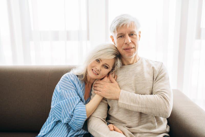 Rijpe echtgenoot en vrouwenzitting op laag en omhelzingen stock foto's