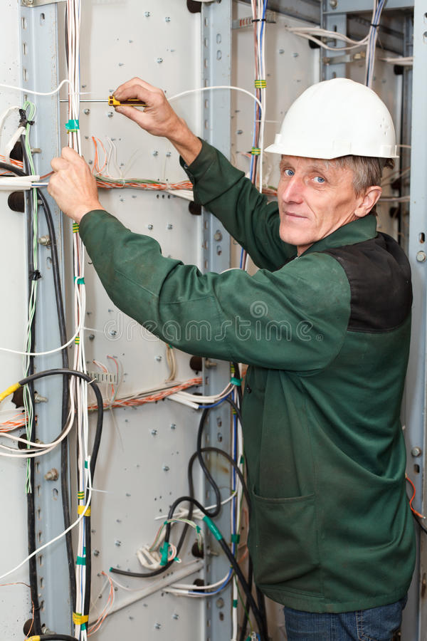 Rijpe elektricien die in bouwvakker met kabels werkt stock afbeelding