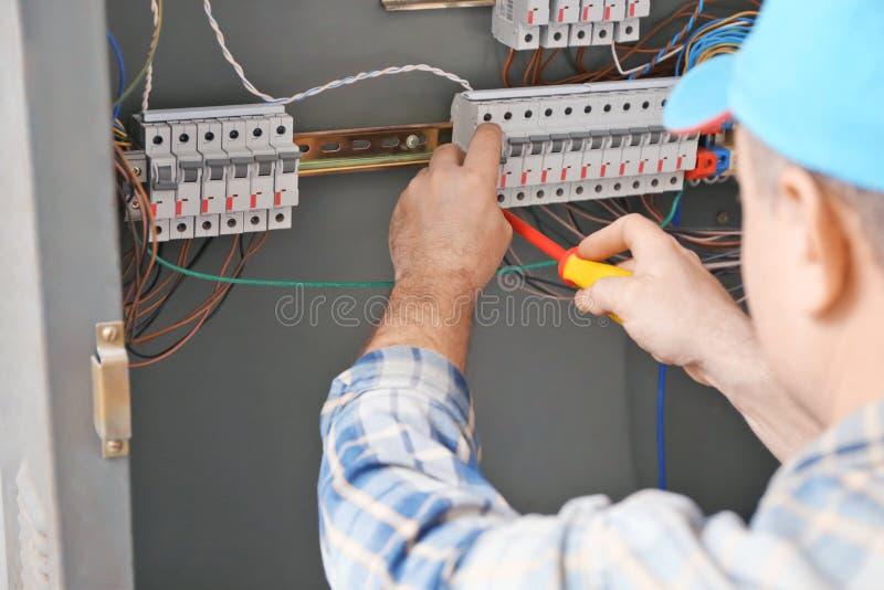 Rijpe elektricien die distributieraad herstelt stock foto's
