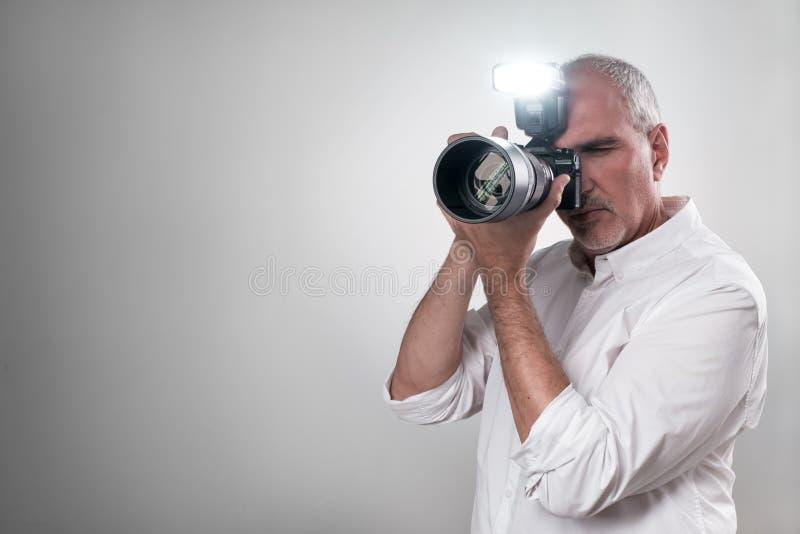 Rijpe Europese Italiaanse mens die een professionele mirrorless camera met het werk flits met behulp van royalty-vrije stock foto's
