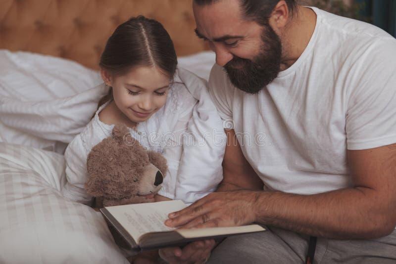 Rijpe gebaarde mens die thuis met zijn kleine dochter rusten royalty-vrije stock afbeelding