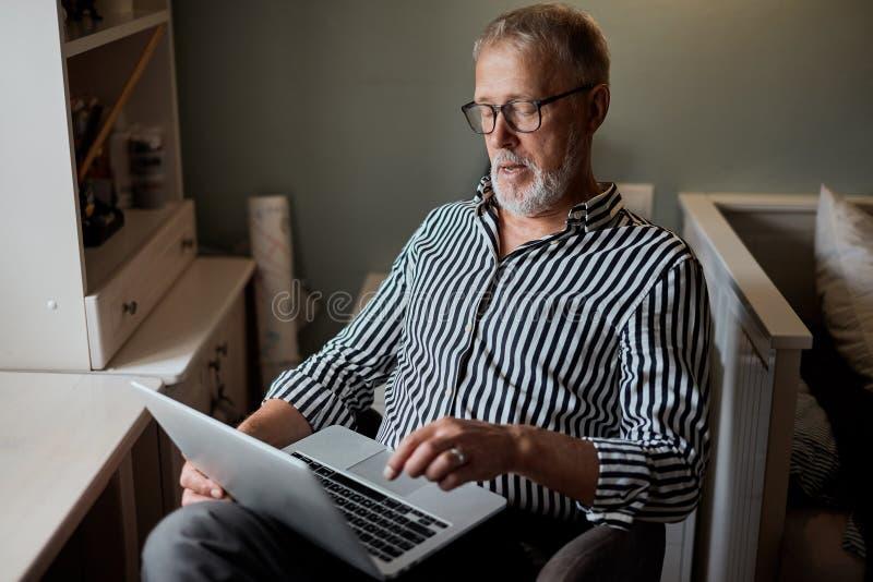 Rijpe gebaarde mens die van huis met laptop werken het zitten bij bureau dichtbij venster stock afbeeldingen