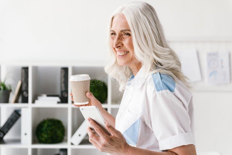Rijpe gelukkige vrouw het drinken koffie die mobiele telefoon met behulp van royalty-vrije stock foto