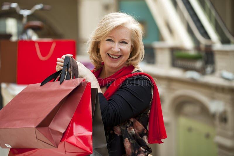 Rijpe gelukkige vrouw met het winkelen zakken royalty-vrije stock fotografie