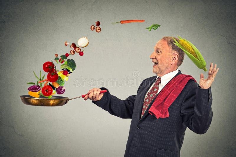 Rijpe gelukkige zakenman kokende groenten met een pan stock fotografie