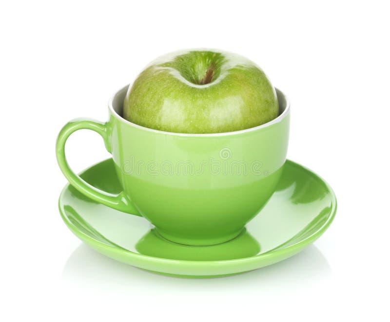 Rijpe groene appel in theekop stock afbeelding