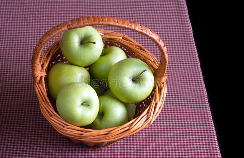 Rijpe groene appelen in bruine rieten mand op rood geruit Schots wollen stoftafelkleed op zwarte achtergrond stock foto's