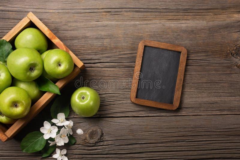 Rijpe groene appelen in houten vakje met tak van wit bloemen en schoolbord op een houten lijst stock foto's