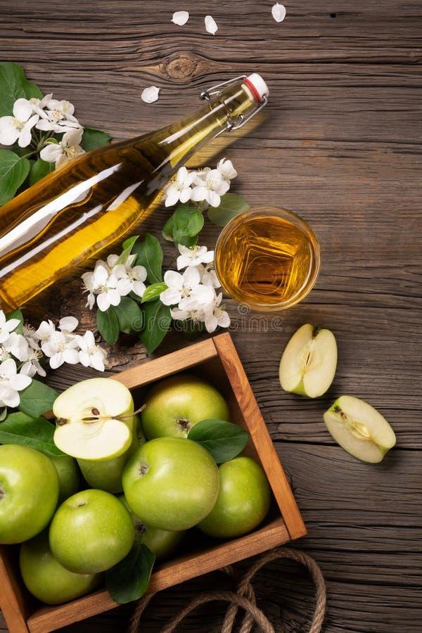 Rijpe groene appelen in houten vakje met tak van witte bloemen, glas en fles cider op een houten lijst royalty-vrije stock foto's