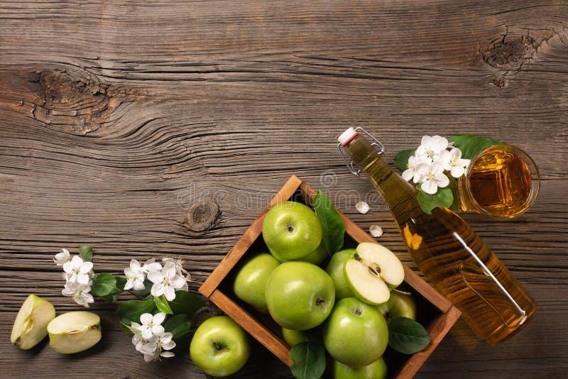 Rijpe groene appelen in houten vakje met tak van witte bloemen, glas en fles cider op een houten lijst stock afbeelding