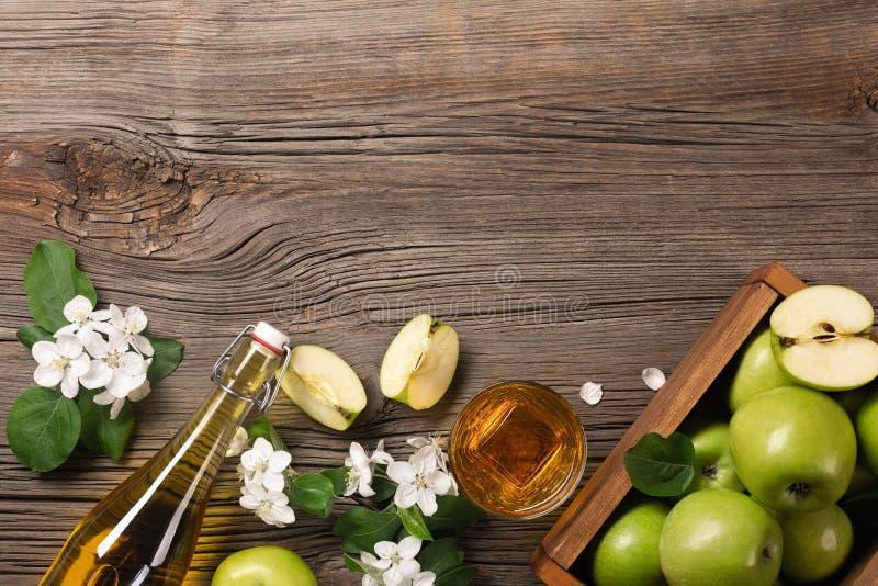 Rijpe groene appelen in houten vakje met tak van witte bloemen, glas en fles cider op een houten lijst royalty-vrije stock fotografie