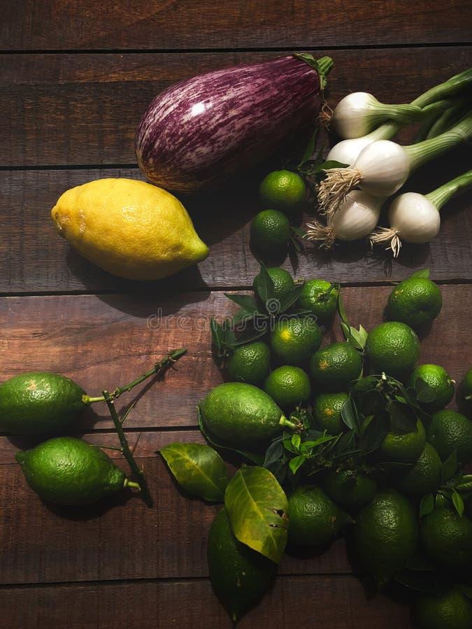 Rijpe groene citroenen, de lenteuien en rode aubergine op houten lijst royalty-vrije stock fotografie