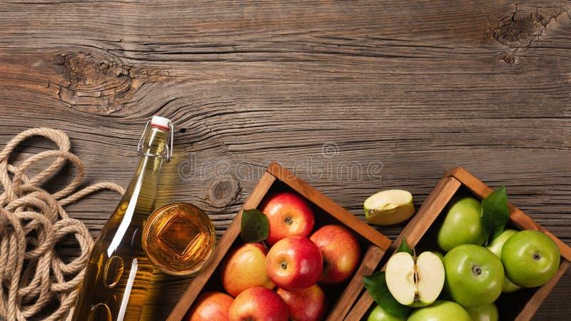 Rijpe groene en rode appelen in houten vakje met tak van witte bloemen, glas en fles cider op een houten lijst royalty-vrije stock foto