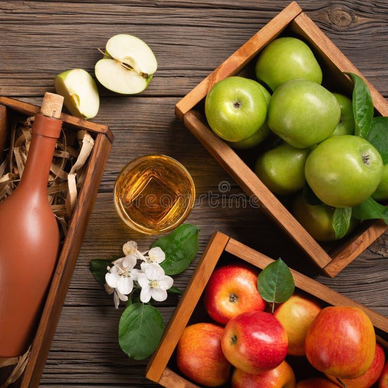 Rijpe groene en rode appelen in houten vakje met tak van witte bloemen, glas en fles cider op een houten lijst stock foto's