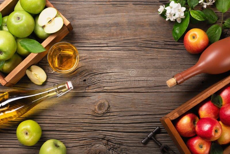 Rijpe groene en rode appelen in houten vakje met tak van witte bloemen, glas en fles cider op een houten lijst royalty-vrije stock foto's