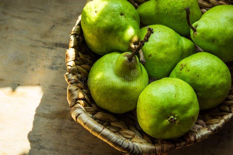Rijpe groene organische peren in uitstekende rieten mand op oude houten keukenlijst, zonlichtvlekken, rustieke stijl royalty-vrije stock fotografie