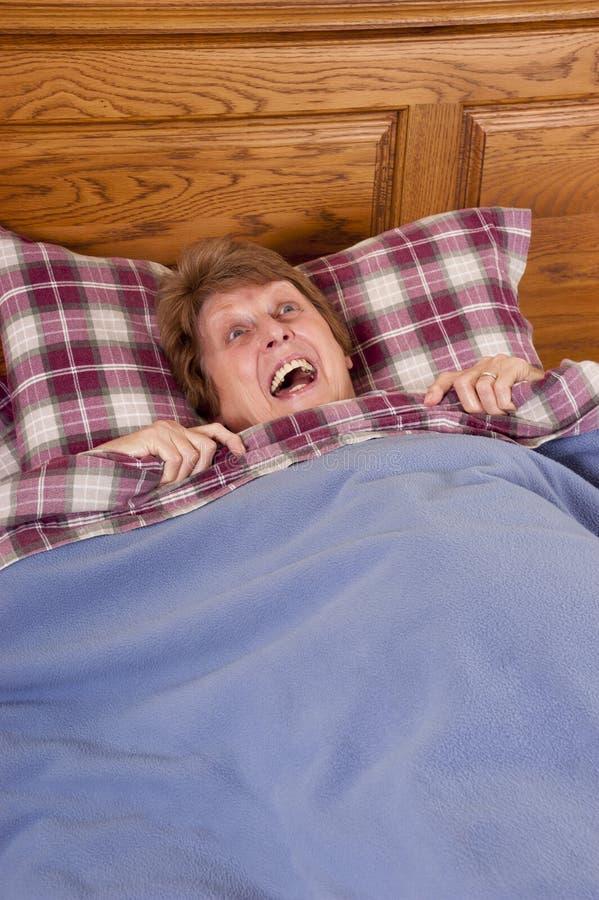 Rijpe Hogere Doen schrikken Vrouw, Bang gemaakt in Bed stock afbeeldingen