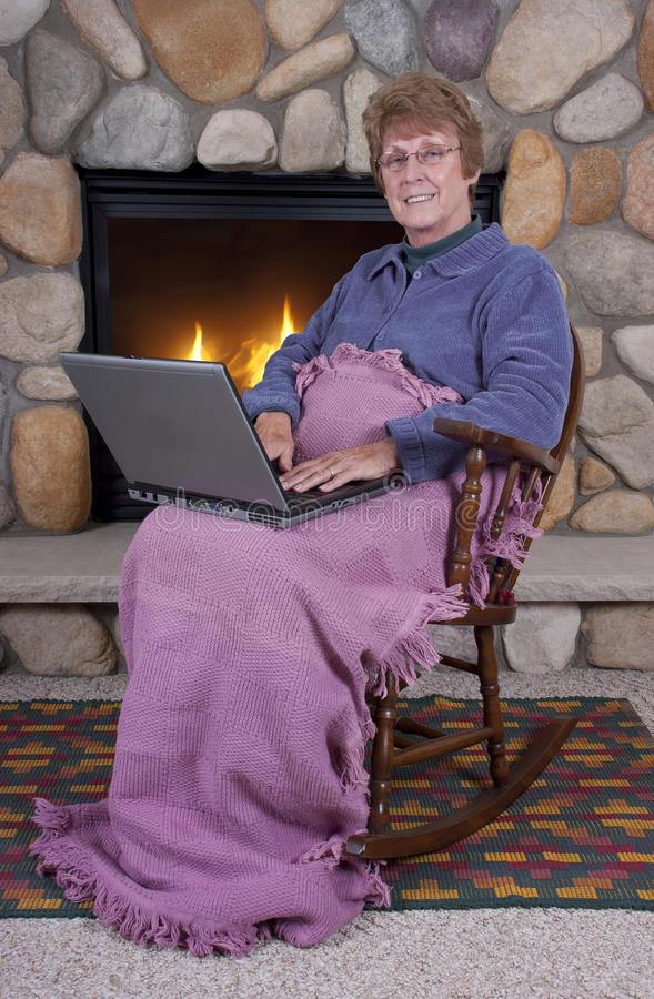 Rijpe Hogere Laptop van Kerstmis van de Vrouw door Open haard royalty-vrije stock afbeeldingen