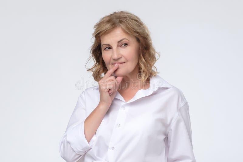 Rijpe Kaukasische ernstige vrouw die over iets denken stock afbeelding