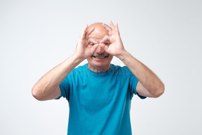 Rijpe Kaukasische mens die uilteken met vingers tonen Het maken van grappig grimas Heb een goede stemming stock foto