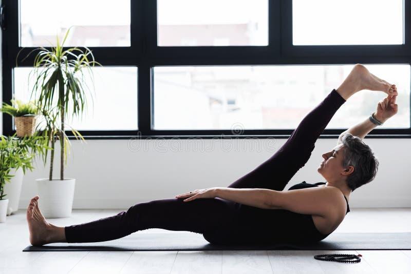 Rijpe Kaukasische vrouw het praktizeren yoga op woonkamervloer stock afbeeldingen