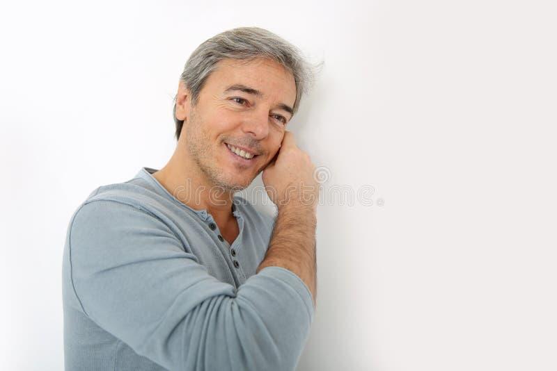 Rijpe knappe mens die op muur leunen stock foto