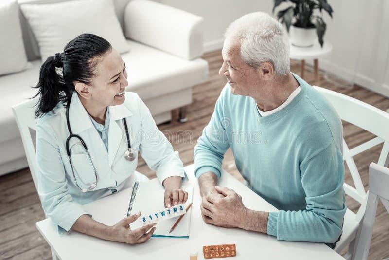 Rijpe leuke verpleegster die pillen geven aan de patiënt en het glimlachen stock afbeeldingen