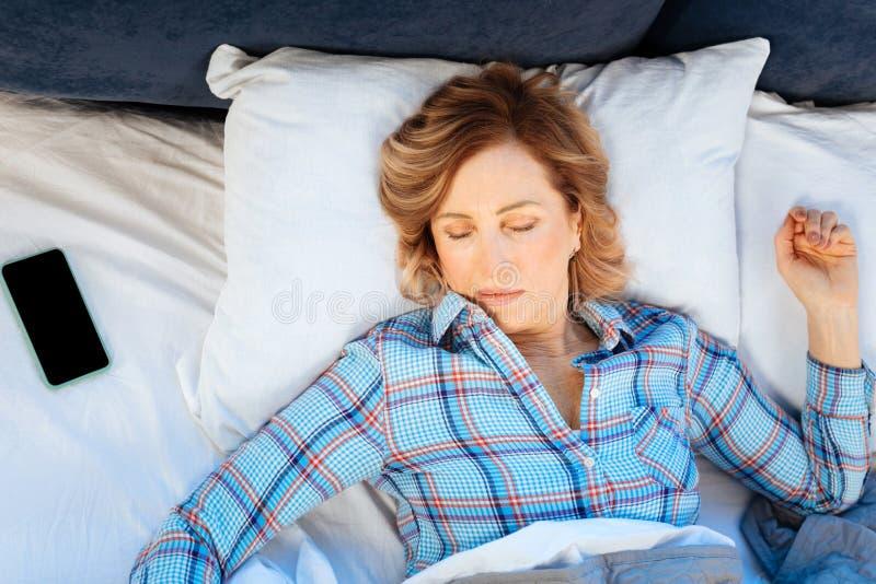 Rijpe licht-haired vrouw die in geruite pyjama haar handen uitspreiden royalty-vrije stock foto's