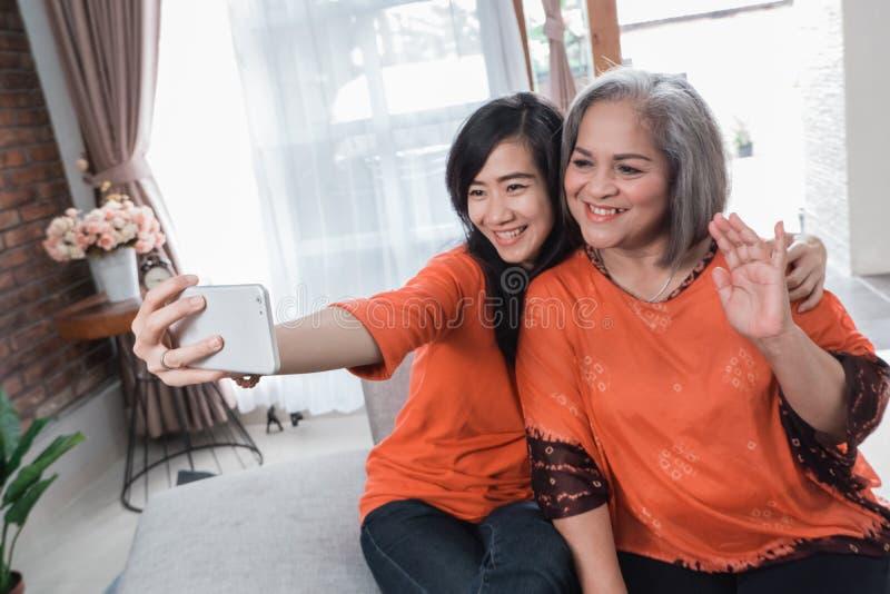 Rijpe mamma en daughter do selfie stock fotografie