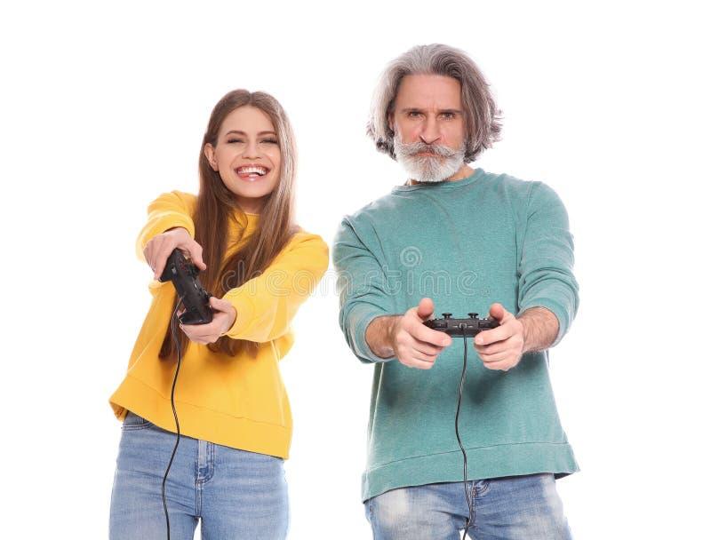 Rijpe man en jonge vrouw het spelen videospelletjes met controlemechanismen stock foto's
