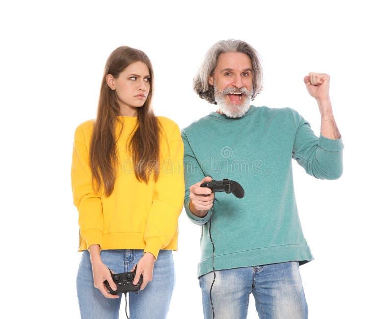 Rijpe man en jonge vrouw het spelen videospelletjes met ge?soleerde controlemechanismen royalty-vrije stock fotografie