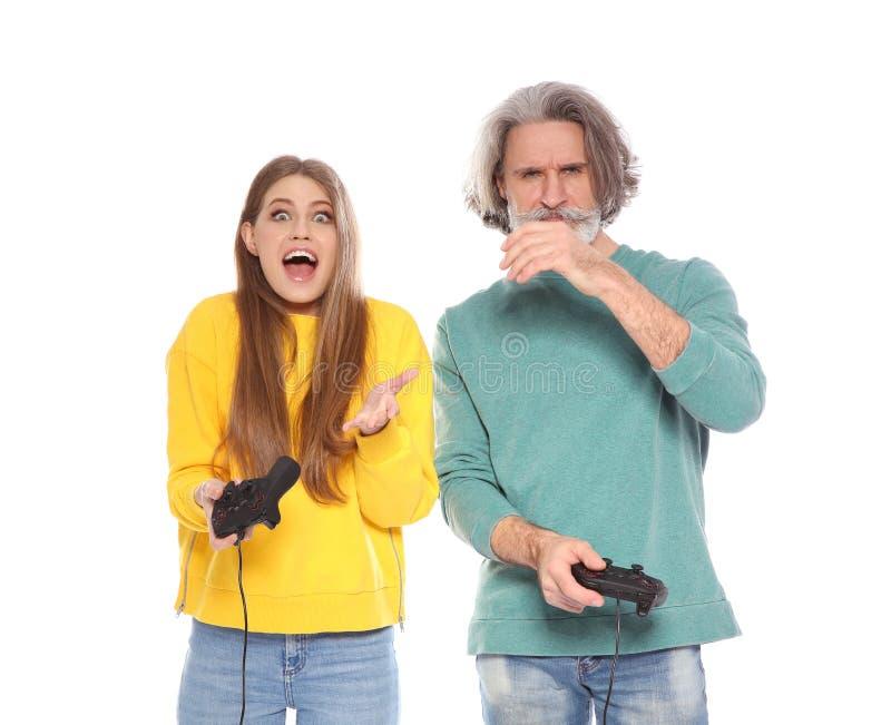 Rijpe man en jonge vrouw het spelen videospelletjes met ge?soleerde controlemechanismen royalty-vrije stock afbeelding