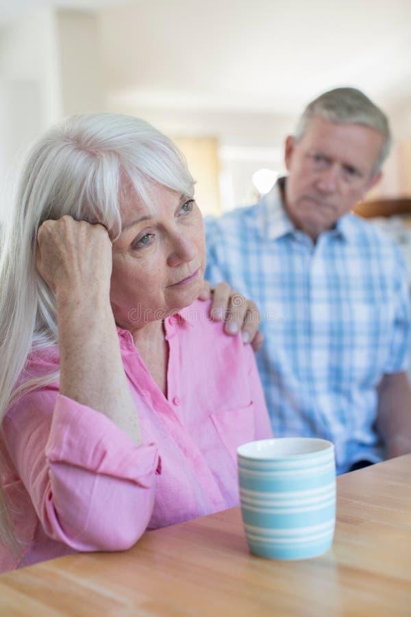 Rijpe Man Troostende Vrouw met Depressie thuis royalty-vrije stock afbeelding