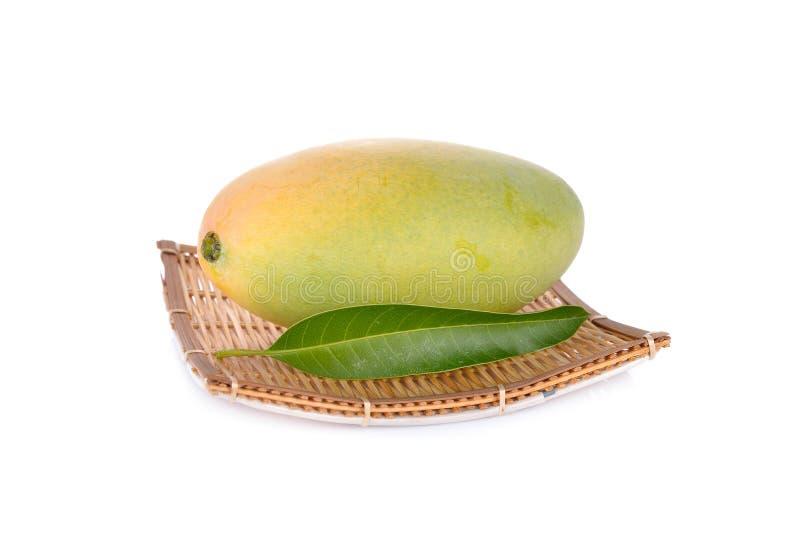 Rijpe mango op bamboeplaat met blad en op witte achtergrond royalty-vrije stock foto's