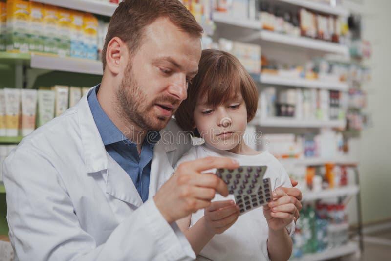 Rijpe mannelijke apotheker die weinig jongen helpen bij drogisterij stock afbeeldingen