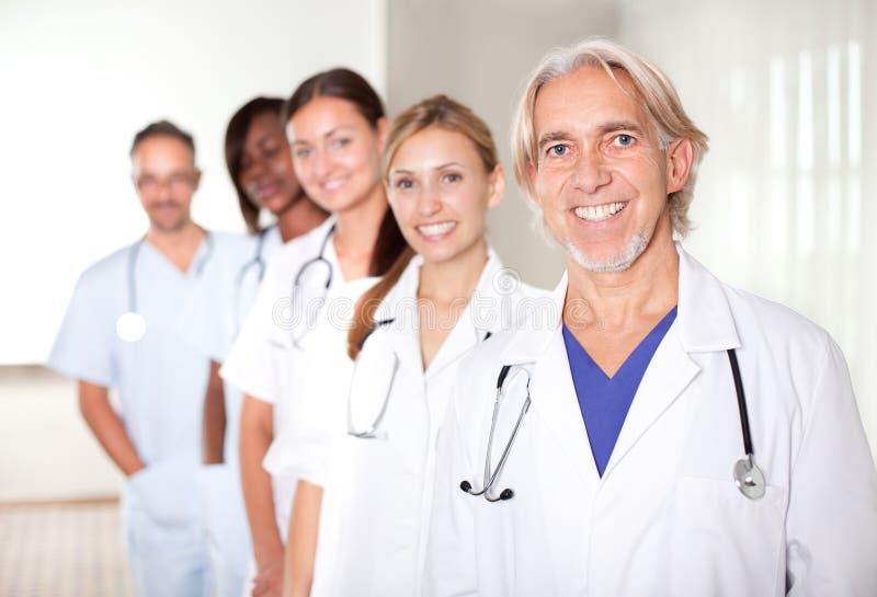 Rijpe mannelijke arts met zijn team van collega's stock fotografie