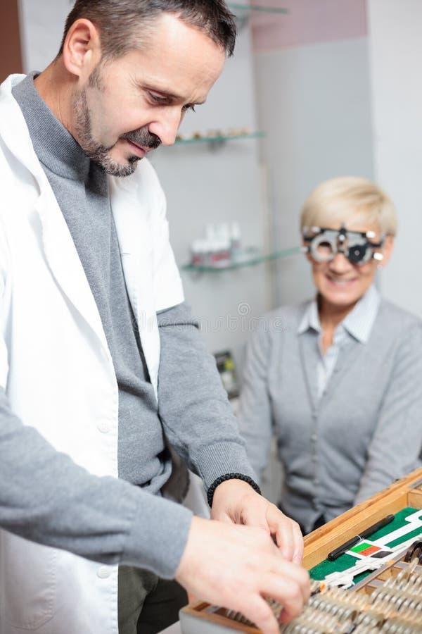 Rijpe mannelijke oftalmoloog die hogere vrouwelijke patiënt in een kliniek onderzoeken, die diopter lenzen kiezen van een doos stock afbeeldingen