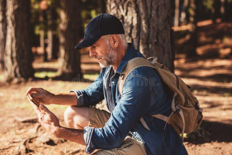 Rijpe mannelijke wandelaar die digitale tablet voor navigatie gebruiken stock foto