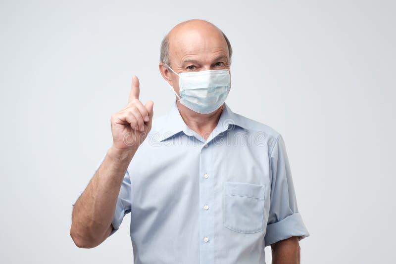 Rijpe mens in beschermend masker die vinger benadrukken stock fotografie