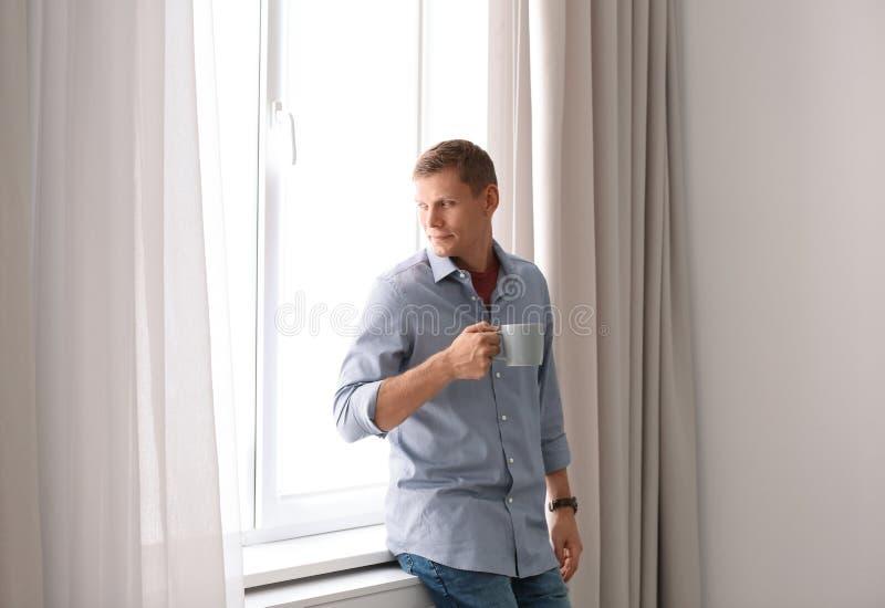 Rijpe mens dichtbij venster met open gordijnen stock foto
