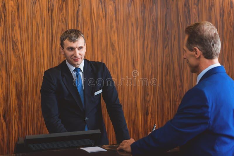 Rijpe mens die aan receptionnist communiceren royalty-vrije stock foto