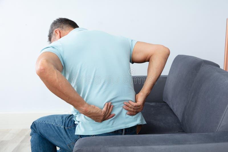 Rijpe mens die aan rugpijn lijden stock foto